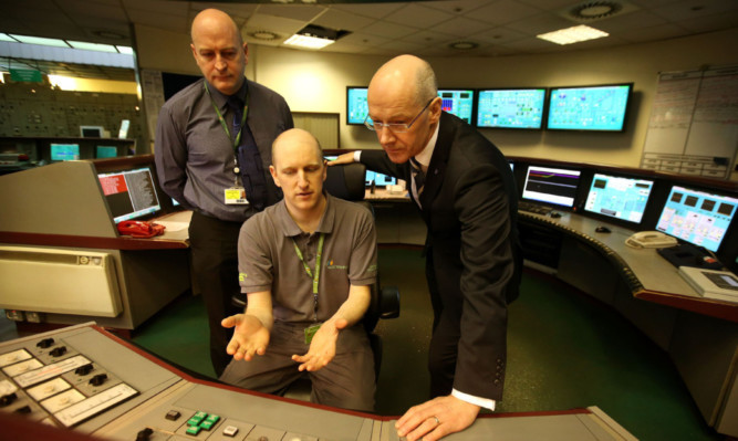 Deputy First Minister John Swinney, right, talks to staff in the control room during a visit to Longannet power station in Fife.