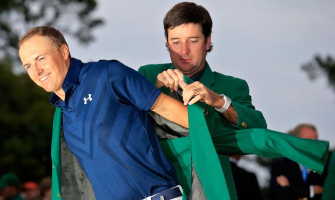 Former champion Bubba Watson presents Jordan Spieth with the green jacket.