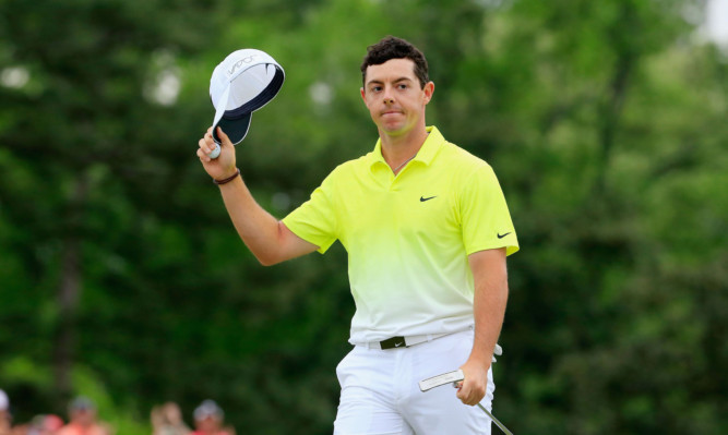 Rory McIlroy waves to the gallery on the 18th green.