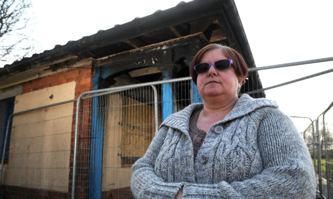 Irene Shearer, chairwoman of the Friends of Baxter Park, beside the fire-damaged pavilion.