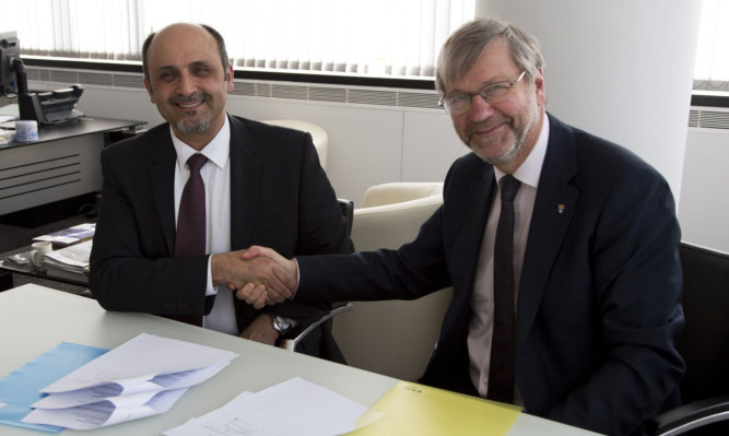 Dr Faisal M Al-Mohanna Abaalkhail from the Saudi Arabian cultural attache shakes hands on the agreement with Professor Pete Downes, principal and vice-chancellor of Dundee University.