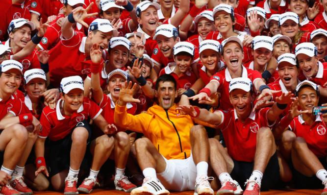 Novak Djokovic celebrates with the ball boys and girls.