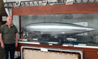 Derek Brown with a model of the R100 airship that he helped to disassemble.