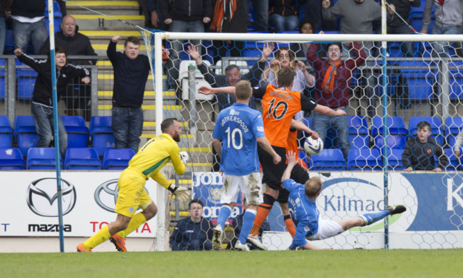 Dundee United's John Rankin (blocked) heads home to put his side ahead.