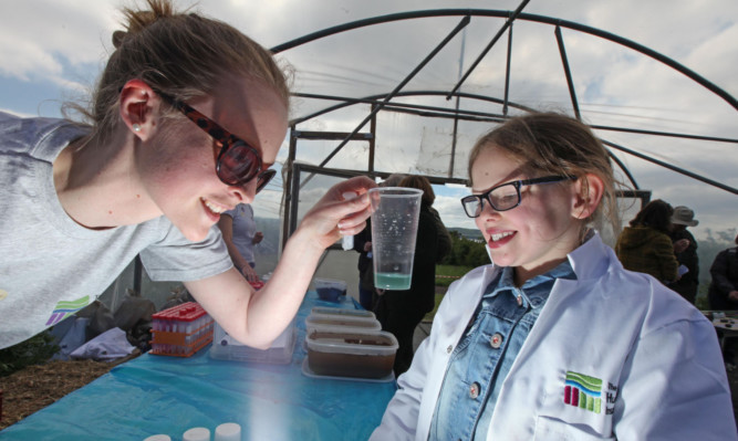 Maisie McCrimmon tries out the crazy chemistry area with a JHI scientist.