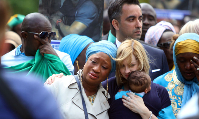 Shekus partner Collette Bell and their son Isaac with mourners at his funeral.