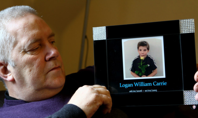 Robert Brown holds a photo of his grandson Logan.