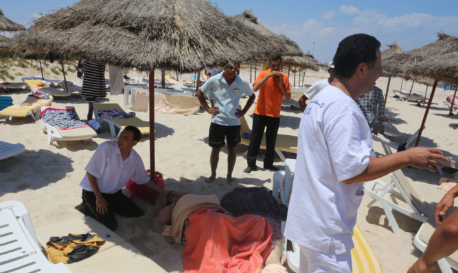 One of the injured is helped on the beach.