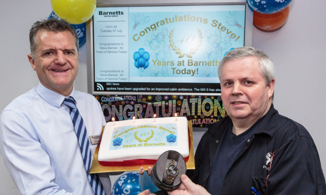 Paul Barnett presents Stephen Benvie with a gold watch and cake for his 40 years of service.