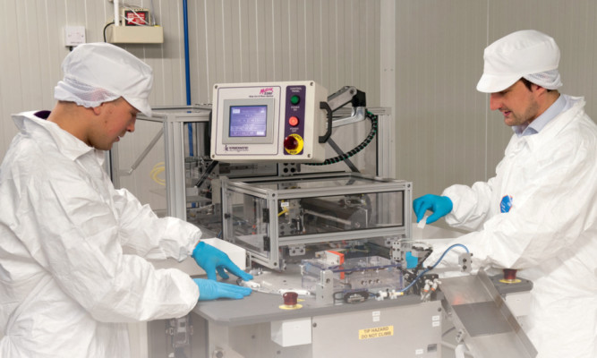 Technicians manufacturing Omegas CD4 hand-held HIV test.