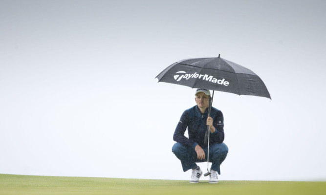 Justin Rose takes shelter again one of the showers at Gullane yesterday.