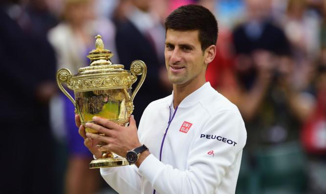 Novak Djokovic celebrates with the trophy.