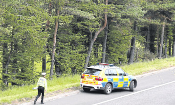 A police car near the site of the car crash which claimed the lives of John Yuill and Lamara Bell.