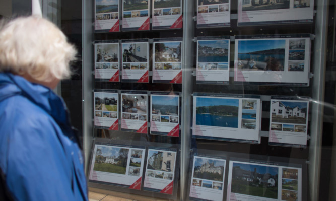 SALCOMBE, ENGLAND - JUNE 01:  A woman looks in an estate agent's window in the seaside town of Salcombe on June 1, 2015 in Devon, England. In a recent study by the Halifax the South Devon resort is now the most expensive seaside town, overtaking Sandbanks in Dorset, with average house prices in the second-home hotspot now reaching £672,874, with prices in the town seeing a massive 69 percent rise over the past decade.  (Photo by Matt Cardy/Getty Images)
