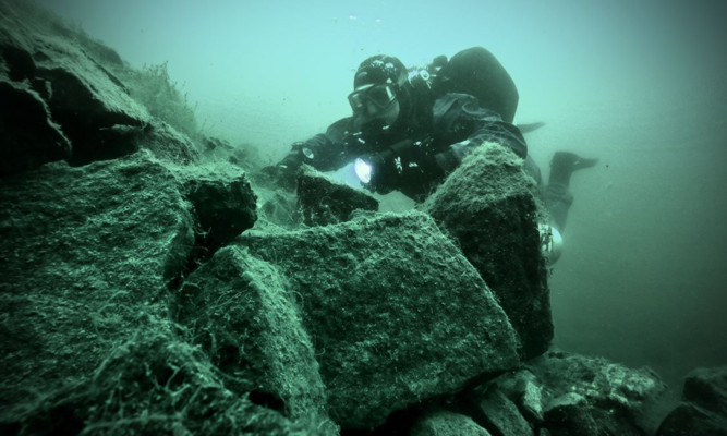 A diver examines rocks in murky waters at the bottom of Prestonhill Quarry.