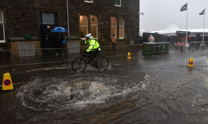 Security staff ride through standing water outside St Andrews, Fife.