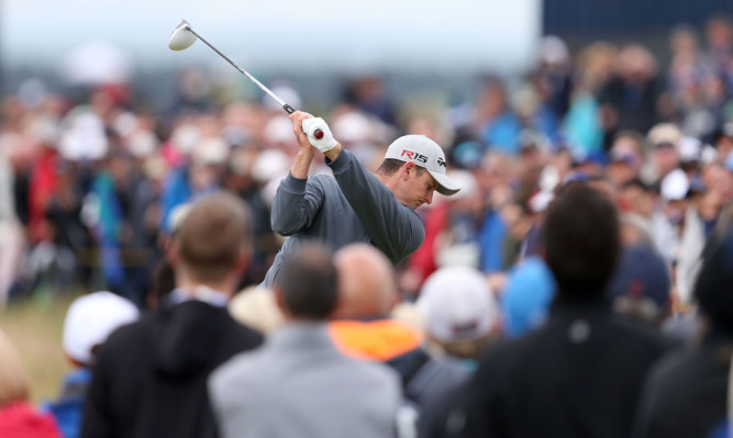 The crowds watches Justin Rose tee off during day two of The Open Championship.