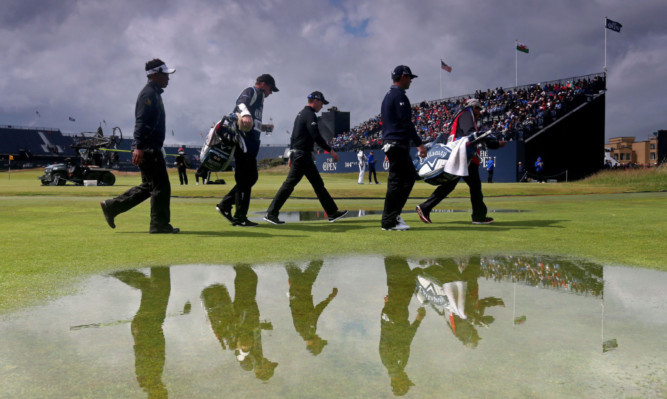 Danny Willett (centre) and partners pass one of the puddles left by yesterday morning's rain.