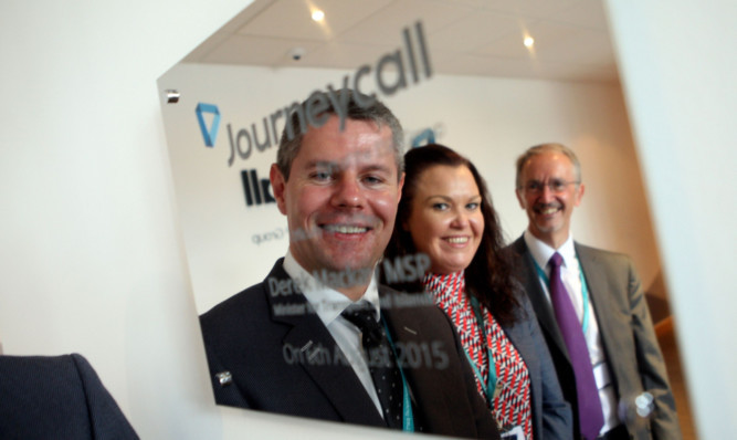 From left: Transport Minister Derek Mackay, Journeycall MD Theresa Wishart and Terry Dunn, CEO of ESP Group, reflected in a plaque to mark the opening.