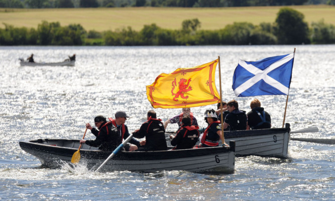 Participants in a boat race recalling Mary, Queen of Scots daring 1568 escape from imprisonment in Loch Leven Castle.