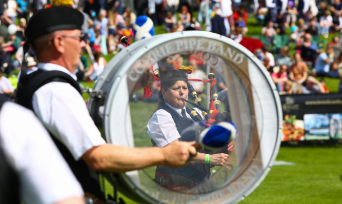Comrie Pipe Band entertains spectators at Crieff Highland Gathering.