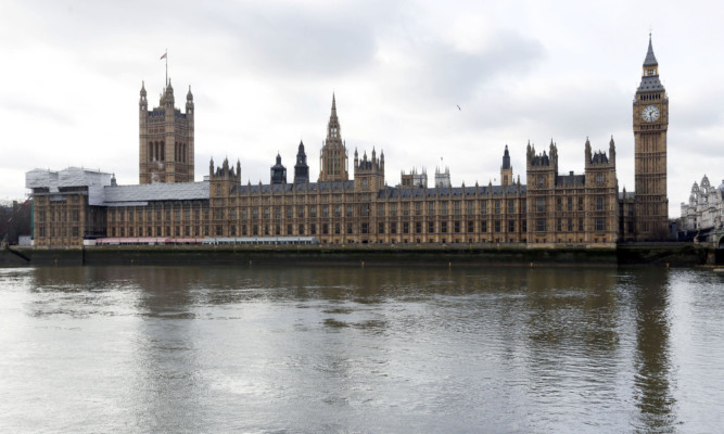 """The Palace of Westminster and Houses of Parliament, London, as there are 100 days to the general election and the parties wheeled out their big guns for a campaign which appears to be shaping up as """"wealth versus health"""". PRESS ASSOCIATION Photo. Picture date: Tuesday January 27, 2015. David Cameron promised he would act """"within the first few days"""" of forming a new government to cut the annual benefits cap introduced by the coalition from £26,000 to £23,000 per household, using the £135 million savings generated to help fund three million apprenticeships by 2020. See PA story POLITICS Election. Photo credit should read: Jonathan Brady/PA Wire"""