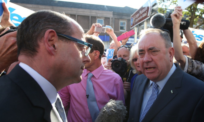 First Minister of Scotland Alex Salmond (centre) is interviewed by the BBC's Nick Robinson (left) whilst on a walkabout in Largs on the last day of campaigning ahead of voting in the Scottish Referendum on September18th