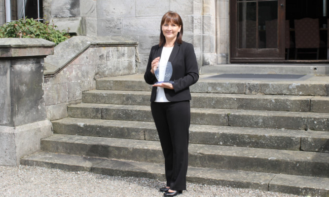 Detective Constable Gail Hill with the Ross Hunt Memorial Trophy for Outstanding Detective Trainee.