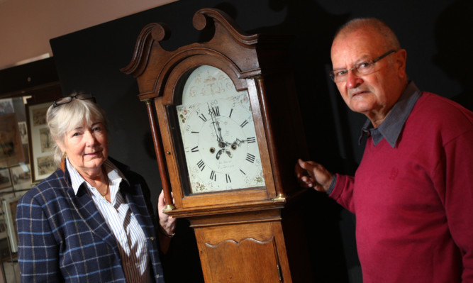 Dr Rheinheimer and wife Rita with the grandfather clock.