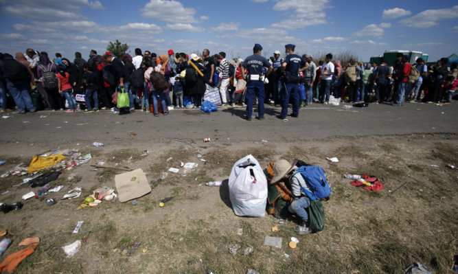 Migrants waiting for the bus which will take to the center for asylum seekers near Roszke in Hungary.