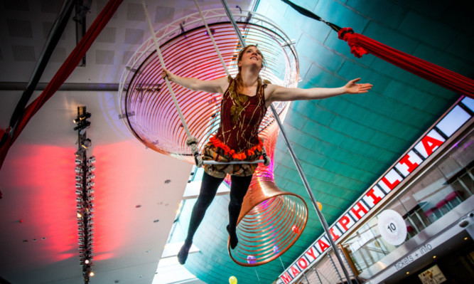 Lucy Power of aerial dance theatre company All or Nothing performs in the concert hall foyer.