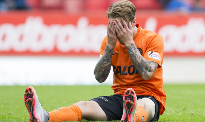 Dejection for United's Adam Taggart at loss to St Johnstone.
