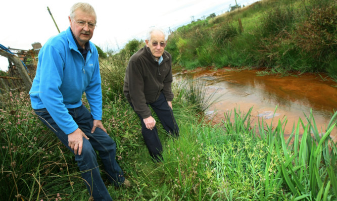 Resident Robert Bennett, left, and David Taylor by a contaminated ditch.