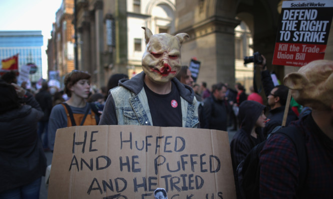 A masked protester outside the Conservative Party conference in Manchester