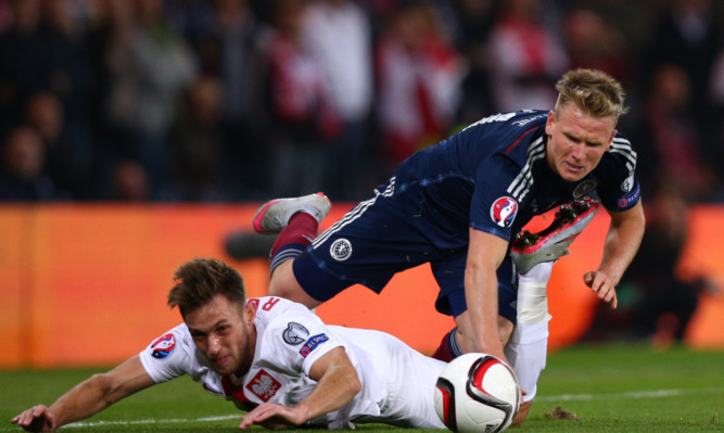 Matt Ritchie of Scotland collides with Maciej Rybus of Poland.