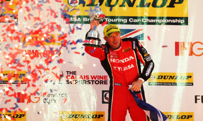 Gordon Shedden celebrates on the podium.