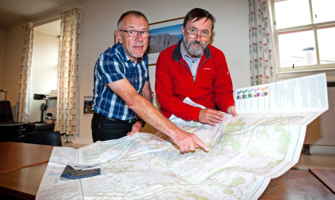 From left: David Gibson and right Neil Reid , from the Mountaineering Council of Scotland examining a map for the site of the controversial windfarm at Dulater Hill near Butterstone.