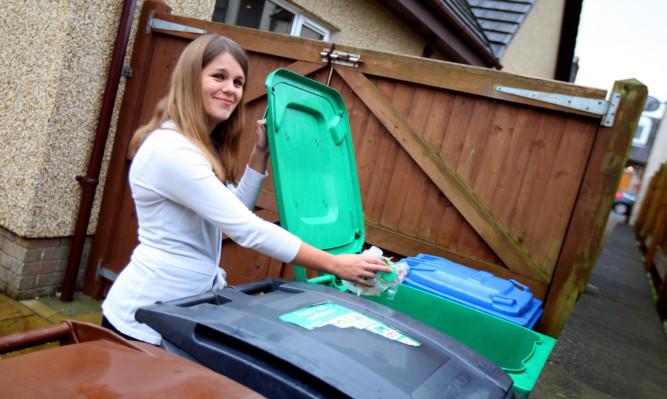 Karen Stewart-Russell, from Markinch,  putting plastics in one of her wheelie bins.