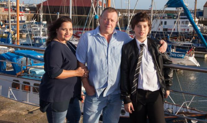 Parents Sunita and Bill Adam with Cameron.