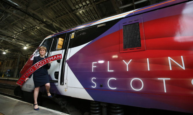 First Minister Nicola Sturgeon beside the Virgin Train Flying Scotsman as its new livery is unveiled at a ceremony at Edinburgh Waverley Station.