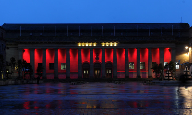 The Caird Hall bathed in red light.