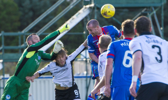 Alan Mannus in the thick of the action at Inverness.