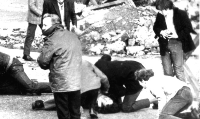 A man receives attention during the shooting, which became known as Bloody Sunday.