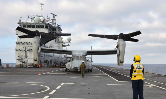 The distinctive US Marine Corps MV-22 Osprey tilt-rotor aircraft are flying off the deck of HMS Ocean during the Cougar 15 deployment, which involves marines based at Arbroath.