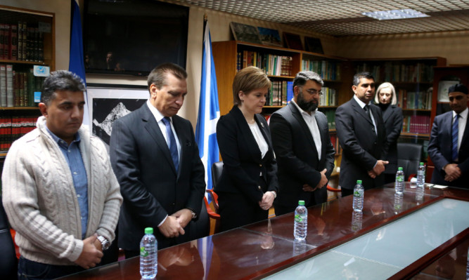 Mosque President Maqbool Rasul (second left) with First Minister Nicola Sturgeon and Mosque Secretary Nabeel Sheikh (fourth left)  as they observe a minute's silence across Europe to mark the victims of Friday's attacks in Paris.