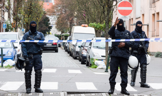 A major action with heavily armed police took place in the Brussels neighborhood of Molenbeek amid a manhunt for a suspect of the Paris attacks.