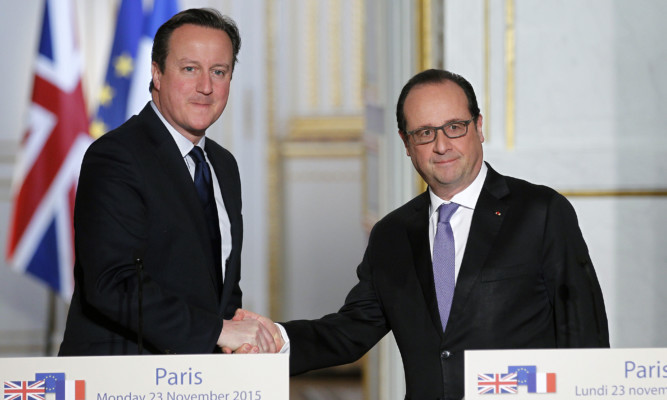 Prime Minister David Cameron shakes hands with French President Francois Hollande.