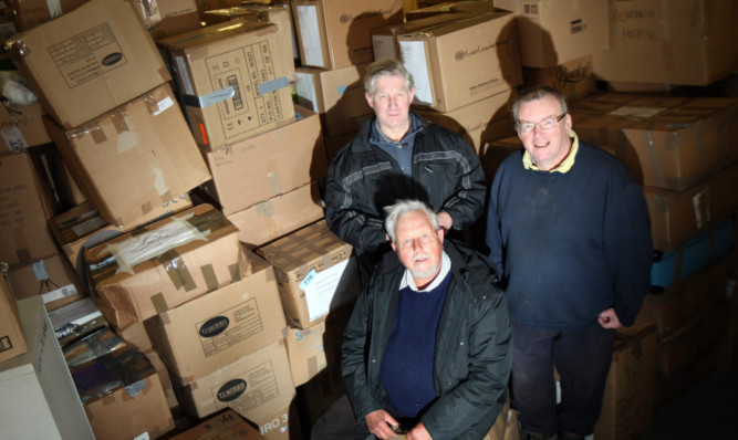 Raven Trust founder John Challis, local organiser David Randall and trustee Alan Lavarock with just a small part of the generous donations that will be loaded and shipped out to schools, homes and hospitals in Malawi.