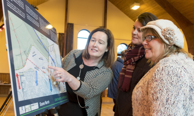 Emelda  MacLean, planning consultant from Emac planning, shows the plans to locals Lee Trussell and Jackie Elliott.
