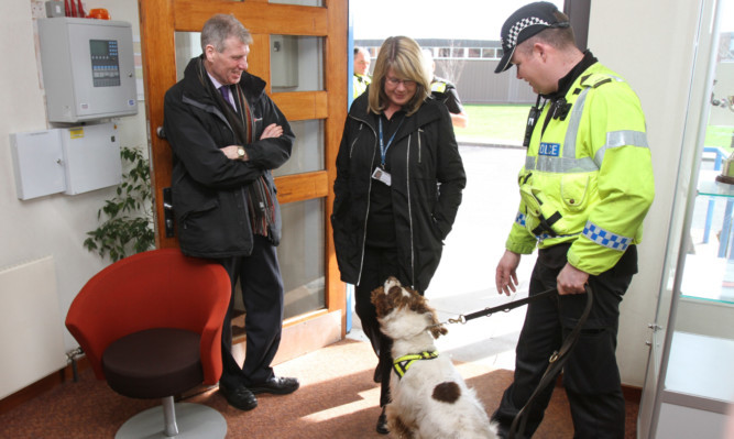 Kenny MacAskill with Constable Ryan Galloway and Buddy who is working, sniffing for drugs, at Baluniefield Police Station, Dundee.